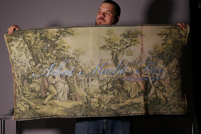 Jason Kreher holding up one of his tapestries